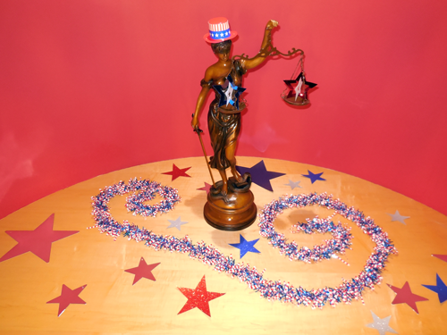 Lady Justice arrayed in patriotic attire and surrounded by stars